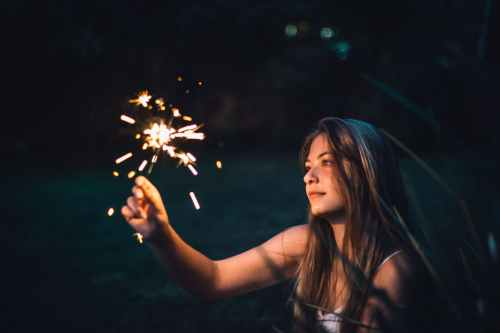 photo of woman holding sparkler