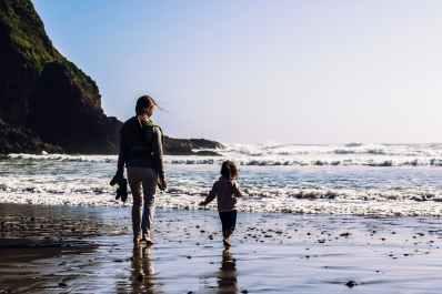 girl and toddler walking at the shore